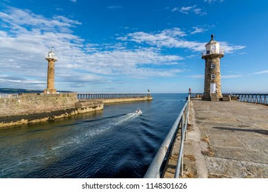 Fishing boat leaving the historic Whitby harbour entrance on a clear summer day with blue sky.