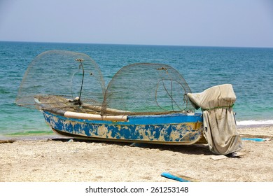 A fishing boat lies with the empty pots on the beach
