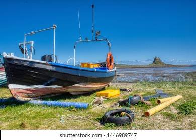 Fishing boat at Lindisfarne, Holy Island in Northumberland with Lindisfarne castle in the background.