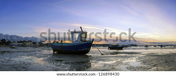 Fishing Boat During Morning Sunrise At Low Tide In The