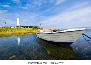 Fishing boat moored on the coast of Baltic Sea in Allinge, Bornholm, Denmark. Chimney of smokehouse in the background.
