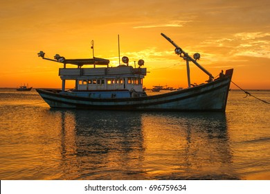 Fishing boat on the background of a golden sunset