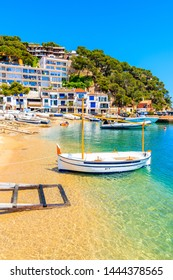 Fishing boat on beach in Llarfanc town with colorful houses in background, Costa Brava, Spain