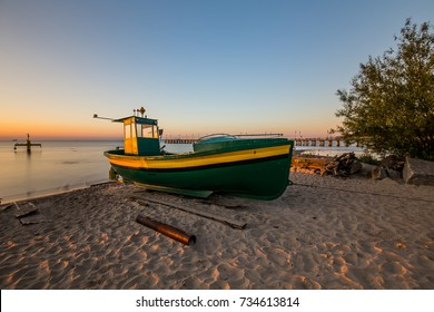 Fishing boat on the beach in Orlowo. Amazing sunrise on the pier at the seaside. Gdynia Orlowo, Poland