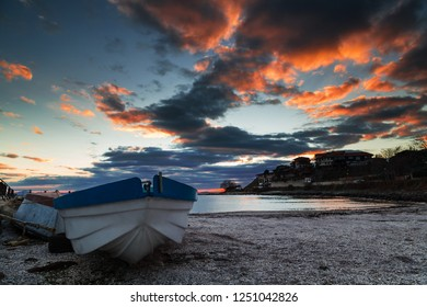 Fishing boat on the beach from shells at sunset
