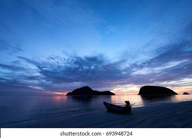 Fishing boat on the beach with sunset background