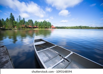 Fishing boat on a calm lake. Across the water are cottages nestled among green trees. In the boat there's a fishing rod