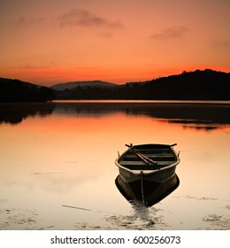 Fishing Boat on a Calm Lake at Sunrise