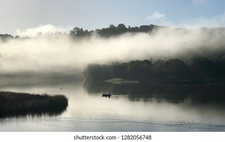 Fishing boat on fog covered lake