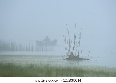 fishing boat on the lake in foggy morning