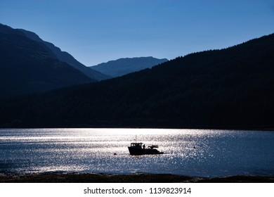 Fishing boat on Loch Long at sunset. Arrochar village, Argyll and Bute, Scotland, UK.
