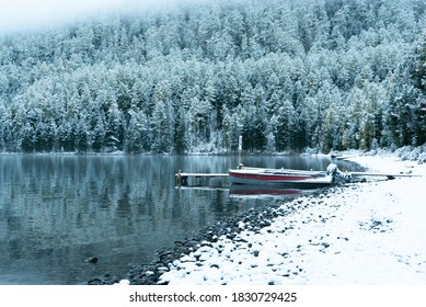 fishing boat on a mountain lake against the backdrop of a winter snow-covered forest and mountains. Multinskie Lakes, Altai, Russia