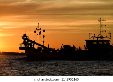 Fishing boat on the river at sunset.