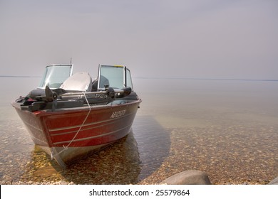 Fishing Boat On Rocky Lake Shore