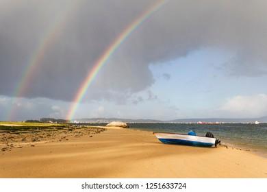 Fishing boat on Sinas beach in Vilanova de Arousa under two stormy rainbows