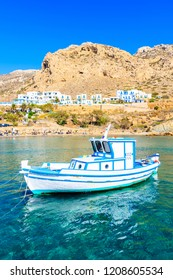 Fishing boat on turquoise sea water with mountains in background in Finiki port, Karpathos island, Greece