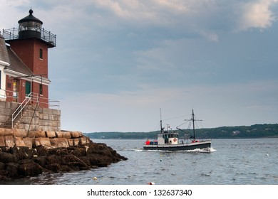 Fishing boat passes by Rockland  Breakwater lighthouse, as it guides mariners into the entrance to Rockland Harbor, in Maine. The brick tower of the beacon lies at the end of a mile long breakwater.