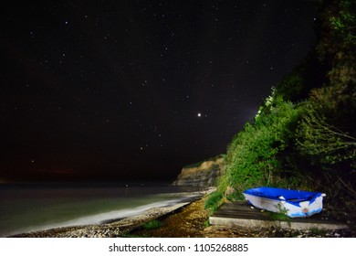 Fishing boat photographed at Shanklin Beach at night with Jupiter in the background sky.