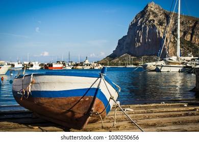A fishing boat in a port in San Vito Lo Capo with Monte Monaco in background, Sicily, Italy