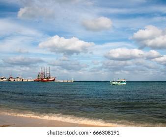 Fishing boat in Puerto Juarez harbor under blue cumulus cloud sky in Cancun Mexico