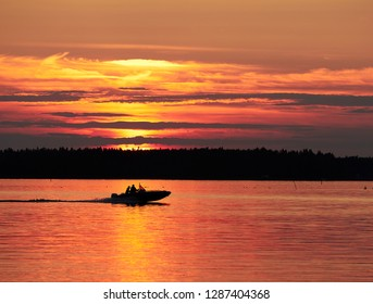A fishing boat and red sunset sky with the setting sun and colorful clouds above a peaceful lake in Vaasa, Finland. The bright disk of the sun is partly hidden by the clouds.