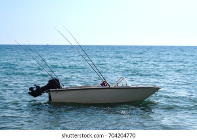 Fishing boat with fishing rods on sea water. Sea vacation.