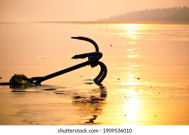 Fishing boat rusty traditional anchor on a beach by the sea.Golden sunlight on sandy beach.