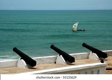 Fishing boat sailing past Cape Coast Castle in Ghana