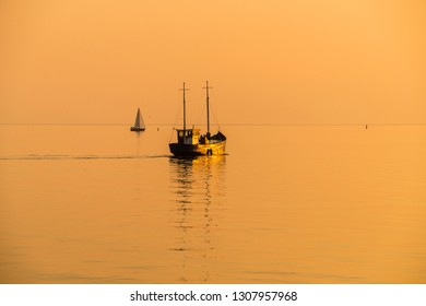 A fishing boat sails out on a summer evening to turn off its nets