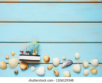 Fishing boat with seashells on blue wooden background. Top view travel or vacation concept. Summer background.