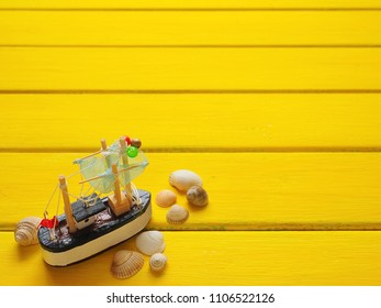 Fishing boat with seashells on yellow background. Travel or vacation concept. Summer background.