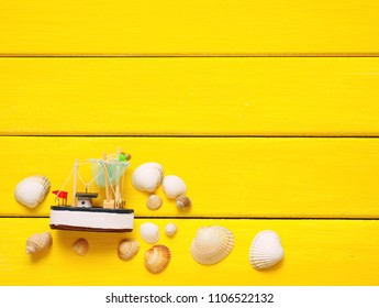 Fishing boat with seashells on yellow background. Top view travel or vacation concept. Summer background.