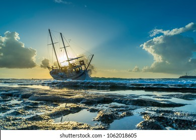 Fishing boat shipwreck or abandoned shipwreck. , Wrecked boat abandoned stand on beach in RHodes Greece