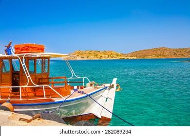 Fishing boat with Spinalonga island as a background. Elounda, Crete, Greece.