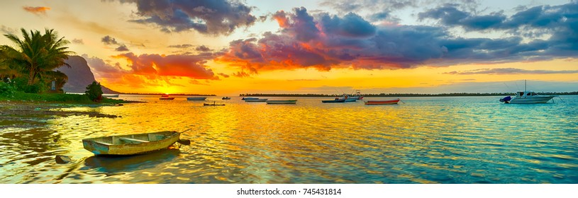 Fishing boat at sunset time. Le Morn Brabant on background. Mauritius. Panorama landscape