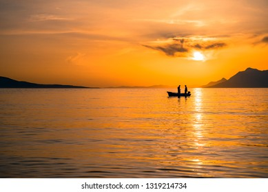 Fishing boat with two silhouetted figures at sunset in the Adriatic sea of the coast of Makarska, Croatia