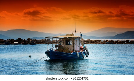 fishing boat under a deep orange sunset sky