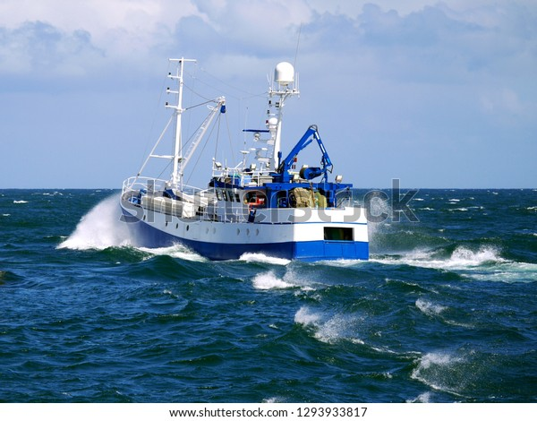Fishing boat underway at speed to fishing grounds.