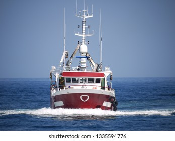 Fishing boat underway at speed to harbour to discharge fish.