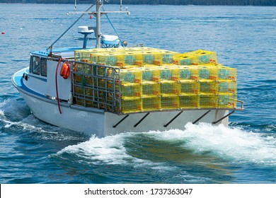 A fishing boat in the waters of Bar Harbor Maine has yellow lobster traps staked four high on a full boat ready to be placed in the water.