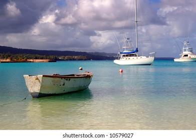 fishing boat and yachts docked at a tropical harbor