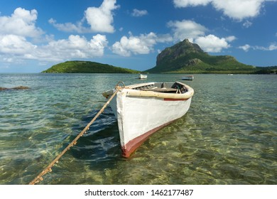 fishing boats against the blue sky, snow-white clouds, mountain and transparent ocean water. Mauritius Island, Indian Ocean