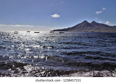 Fishing boats anchored in the bay of the town of Isleta del Moro, in the background the volcanic calderas of Los Frailes, Natural Park of Cabo de Gata, Almería, Andalusia, spain,