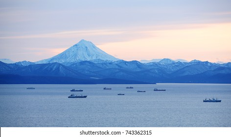 fishing boats in the Bay with the volcano in autumn on Kamchatka