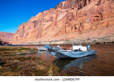 Fishing boats beached on shore of Colorado river near Lees Ferry AZ and Glen Canyon dam.