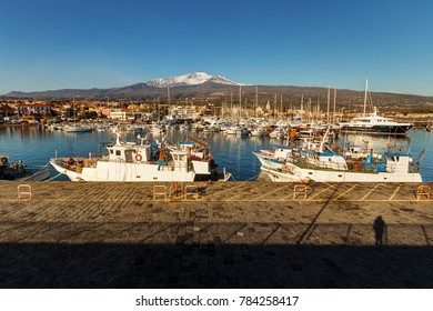 Fishing boats berthed at the Riposto harbour, in Sicily during a sunny day. Etna mount, snow-covered on background.