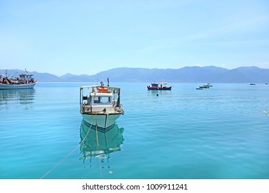Fishing boats in the blue water of Evia Island, Greece