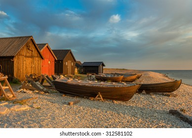 Fishing boats and fishing cabins on the stony beach of Faro, Sweden, in the light of the sunrise