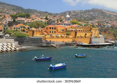 Fishing boats, city beach and ancient fortress. Funchal, Madeira, Portugal