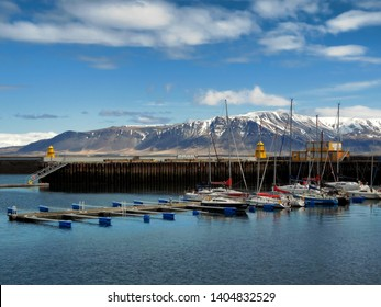 Fishing Boats docked at Faxa Bay Harbor, in Reykjavik Iceland, taken in late May, 2016.  Dock, water, sky, and mountains are in view.